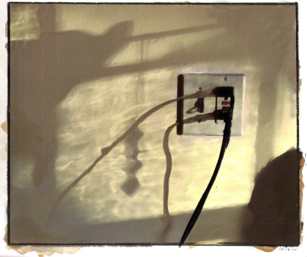 morning light and shadows on a wall with electrical outlet